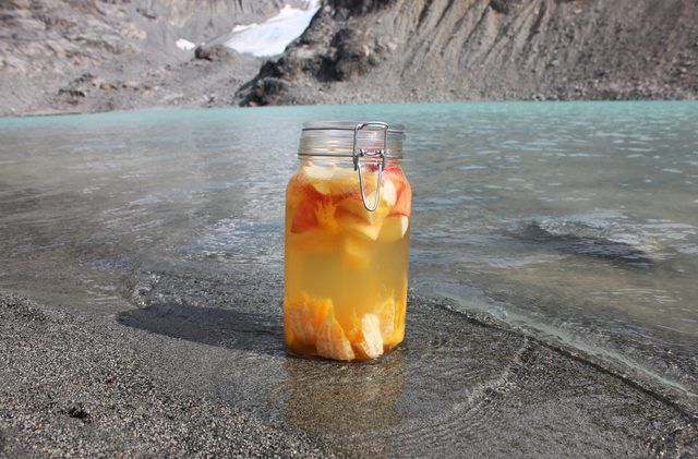 Um grande frasco de pedreiro de sangria frutados sendo refrigerados pela costa de um lago alpino.