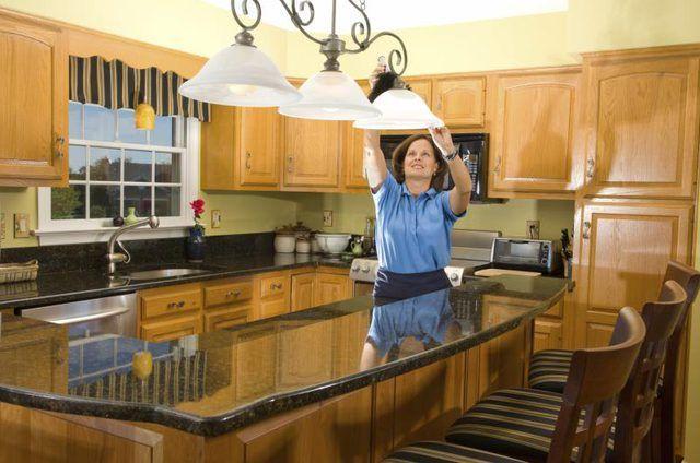 Mulher lâmpada ajuste por cima da cozinha do granito