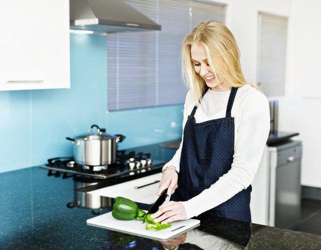 Mulher pimentas na cozinha cortando