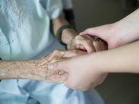 Um fim acima de uma mulher segurando uma mulher idosa`s hands.