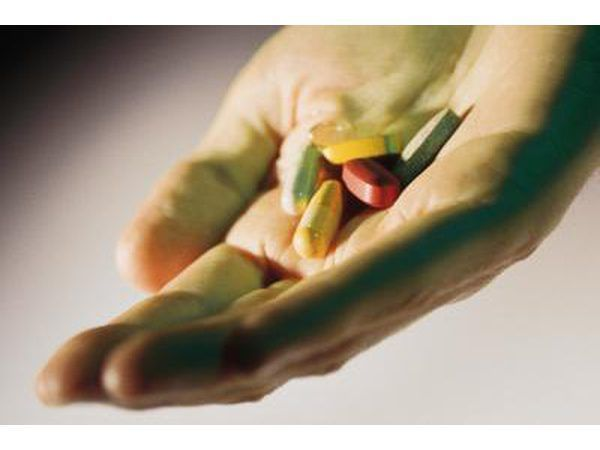 Uma mulher toma suplementos em forma de pílula.