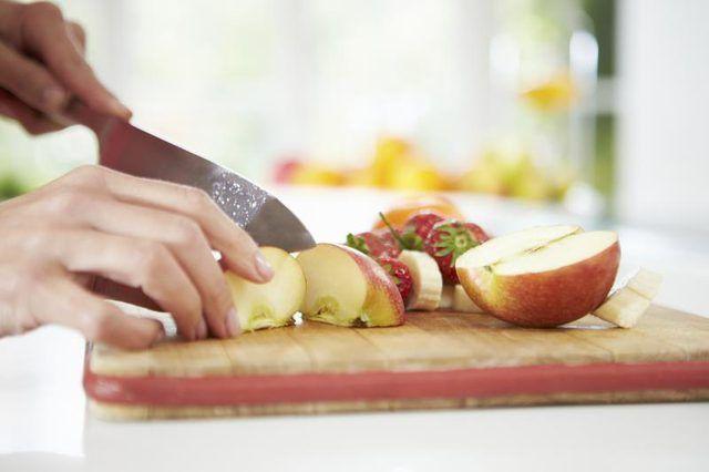 Uma mulher corta uma maçã fresca.