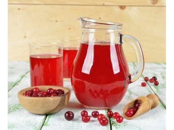 Jarro e copos cheios de suco de cranberry, bem como uma tigela de cranberries em uma mesa