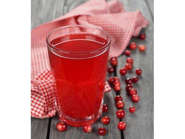 Um copo de suco de cranberry em uma tabela com cranberries