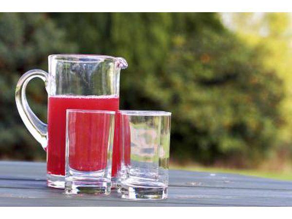 Jarra de suco de cranberry e beber copos em uma mesa de madeira