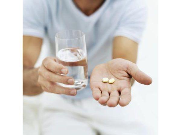 Homem segurando 2 comprimidos e um copo de água.