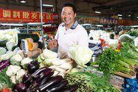 Um vendedor está vendendo verduras no mercado.