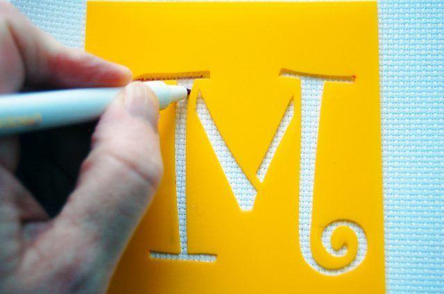 Stenciling uma carta para um tecido.