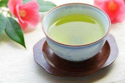 Uma xícara de chá verde quente em uma mesa com flores de corte.