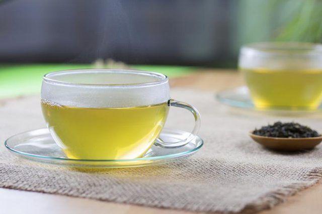 Dois copos de vidro do chá verde quente liso com uma pequena tigela de chá de folhas secas.