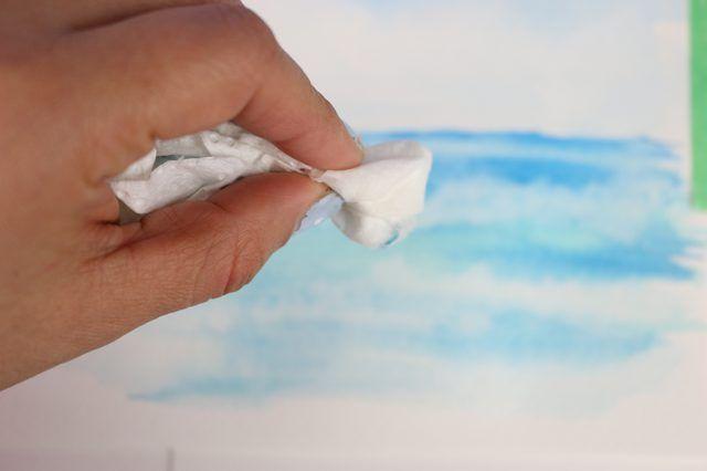 A toalha de papel absorve a tinta molhada para formar nuvens no céu.
