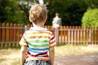 A parte de trás de um menino de pé em um playground.