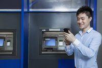 Homem que verific seu telefone na frente de uma máquina ATM.