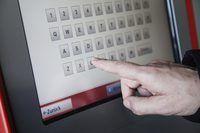 Close-up de uma mão que datilografa em uma tela de menu de quiosque