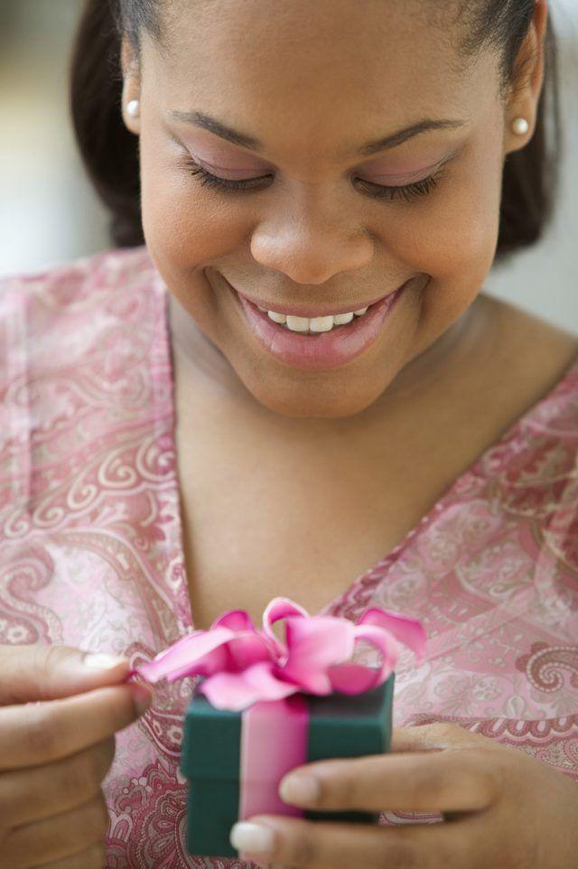 Uma mulher abrindo uma caixa de presente pequena.
