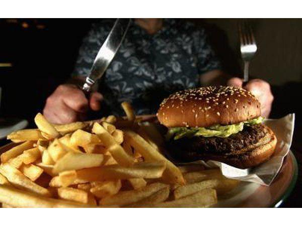 Homem aproximadamente para comer hambúrguer e prato de batatas fritas