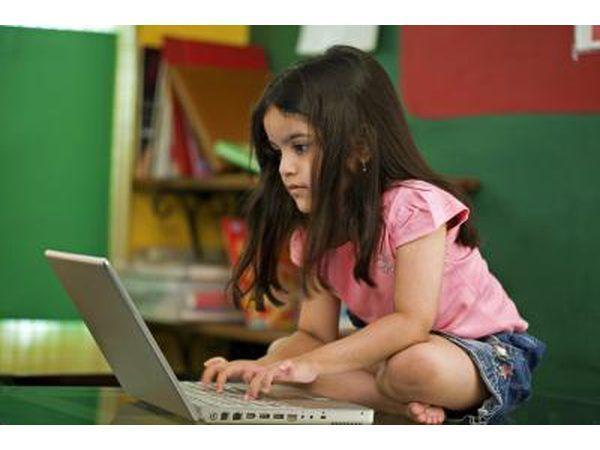 Menina que joga no portátil
