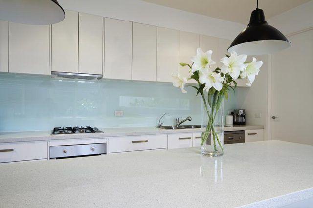 Cozinha moderna com bancadas de granito branco.