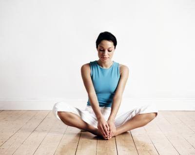 Mulher sentada em uma pose da ioga em um piso de madeira.