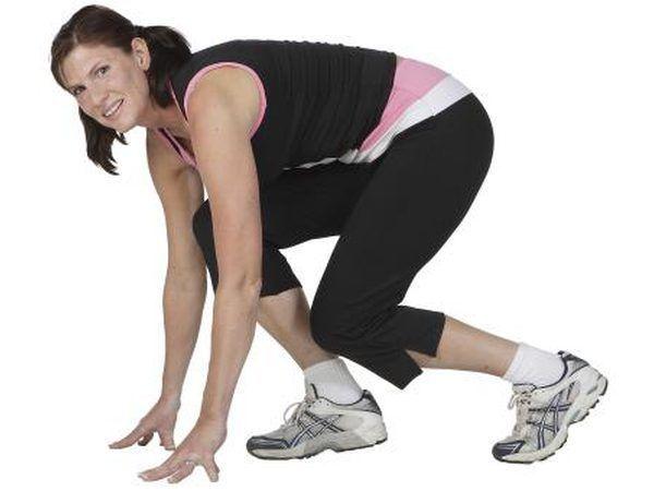 Mulher que faz o exercício de agachamento dentro de casa.