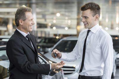 Uma pessoa de vendas de mãos chaves para um cliente.