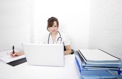 Um médico em sua mesa preparando documentos médicos para o faturamento.