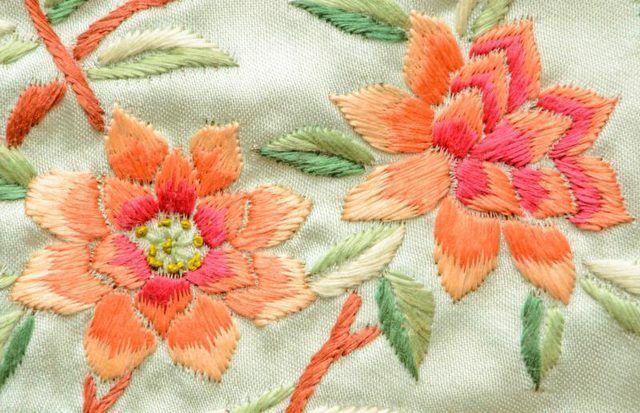 Um close-up de rosa e pêssego bordado flores.