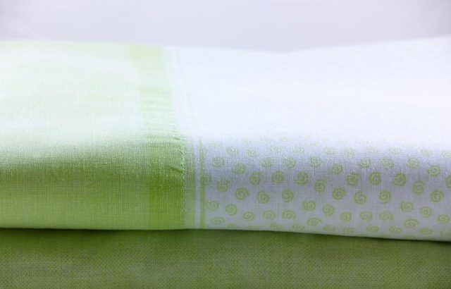 Uma luz lençol verde e branco dobrado.