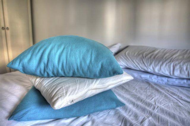 Uma pilha de almofadas azuis e brancos na cama.