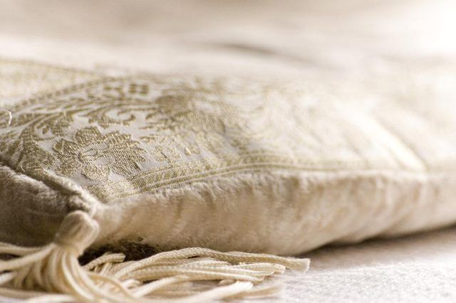 Uma almofada branca que descansa sobre um lençol branco.
