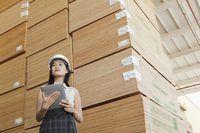 Uma imagem de uma mulher de negócios de pé junto madeira serrada.
