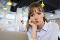 Uma mulher deprimida sentado em um escritório moderno