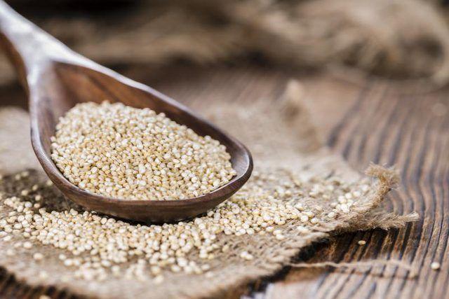 colher de madeira de quinoa seca.