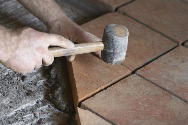 Close up das mãos trabalhando com telha cerâmica