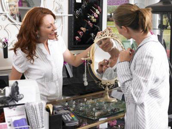 Uma pessoa de vendas ajudar um cliente em uma loja de jóias.