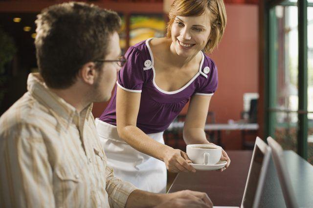 Um servidor restaurante serve café da manhã para um cliente.
