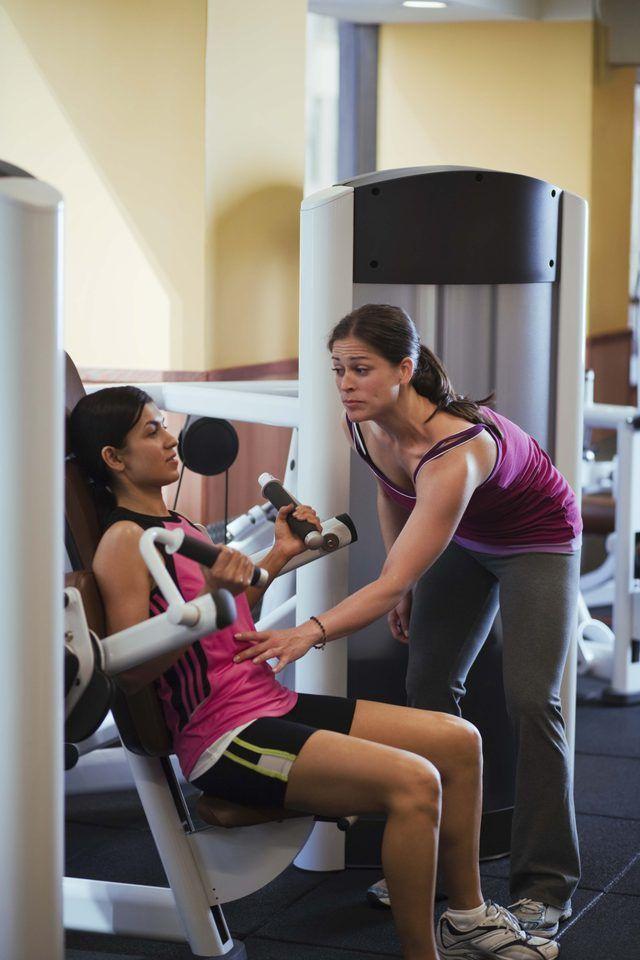 Um personal trainer trabalha com um membro do ginásio.