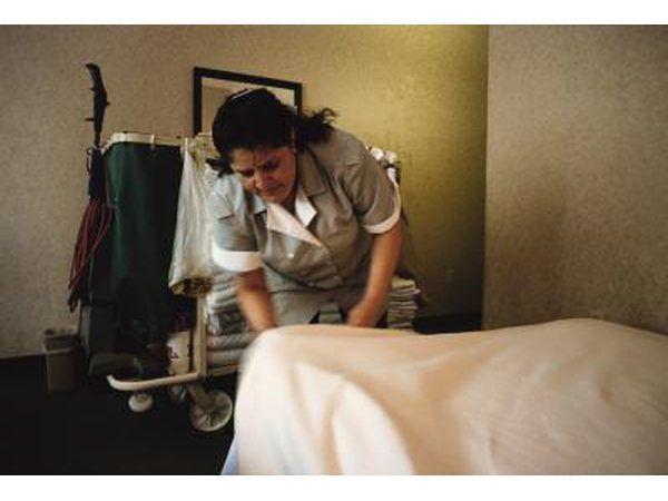 A dona de casa limpa um quarto em um hotel.